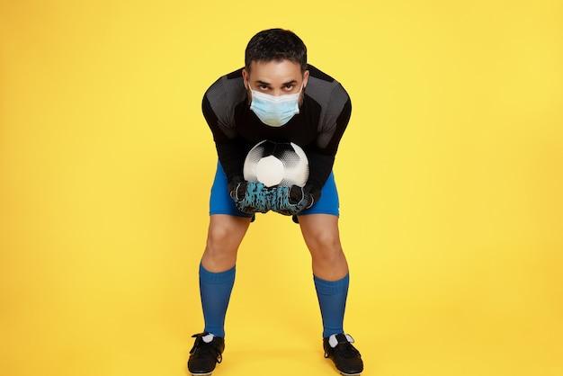 Bramkarz piłki nożnej w masce z powodu pandemii koronawirusa zatrzymujący piłkę rękami na żółtej ścianie