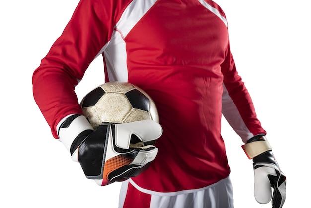 Bramkarz trzyma piłkę na stadionie podczas meczu piłki nożnej na białym tle