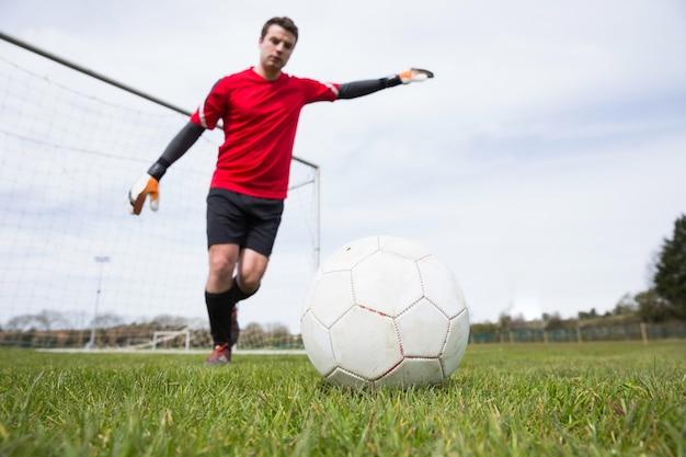 Bramkarz w czerwonej kopanie piłki z dala od bramki
