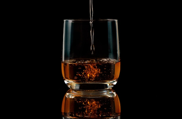 Brandy wlewa się do szklanki na czarnym tle