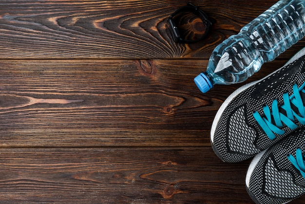 Bransoletka fitness, trampki i butelka wody na ciemnym drewnianym
