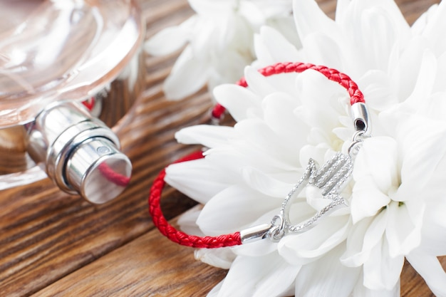 Bransoletka na białym kwiatku i perfumach. piękne miękkie tło z zbliżeniem kobiecych akcesoriów. romantyczna kompozycja kobiecej kadry