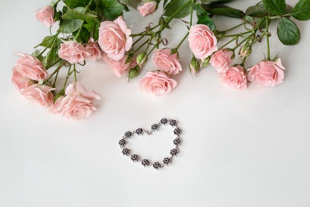 Bransoletka w kształcie serca z klejnotami otoczona jasnoróżowymi różami. prezent na walentynki.