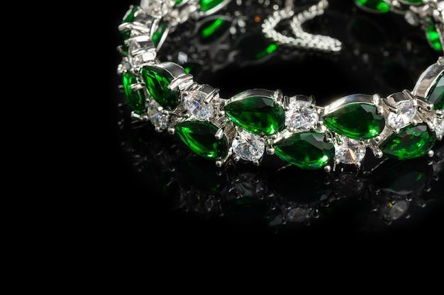 Bransoletka z zielonymi kamieniami na czarnym tle