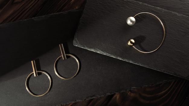 Bransoletka ze złotej perły i złote kolczyki łączą się na kamiennych tacach na ciemnym drewnie
