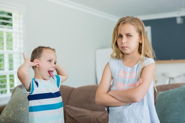 Brat drażni swoją siostrę, stojąc ze skrzyżowanymi rękami