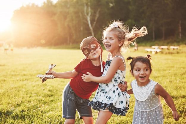 Brat i dwie siostry bawią się razem. troje dzieci bawiących się drewnianym samolotem na zewnątrz