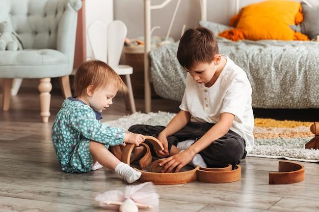 Brat i siostra bawią się drewnianymi zabawkami w pokoju dziecięcym. dzieci bawią się na podłodze projektantem zabawek.