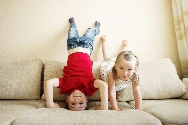 Brat i siostra bawią się na kanapie: chłopiec stoi do góry nogami
