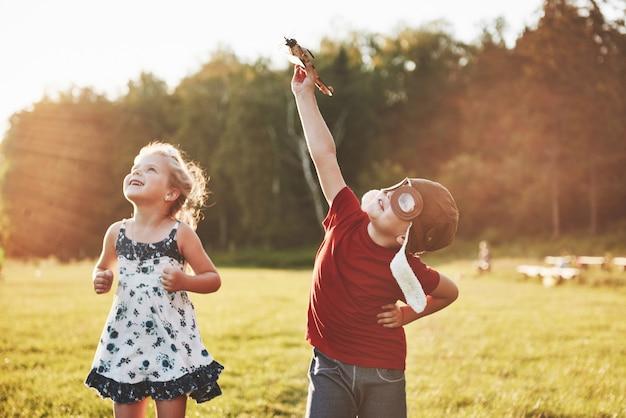 Brat i siostra bawią się razem. dwoje dzieci bawiące się drewniany samolot na zewnątrz