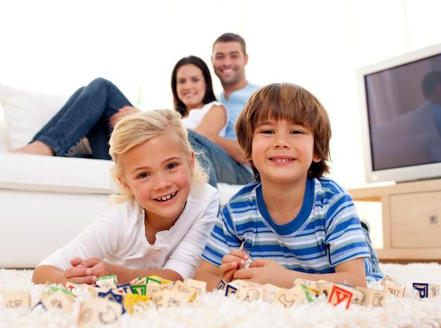 Brat i siostra bawić się z abecadło sześcianami w domu