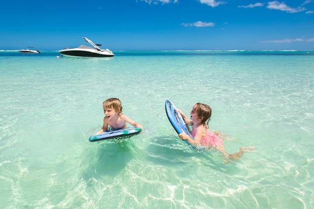 Brat i siostra bliźniaków, aby dobrze się bawić podczas surfowania w oceanie