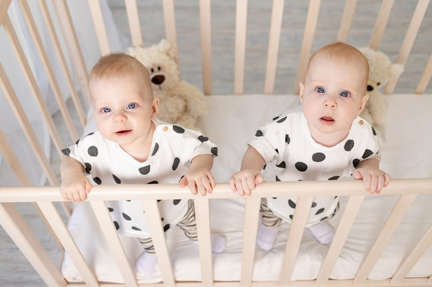 Brat i siostra bliźniaków siedzą w piżamie w łóżeczku