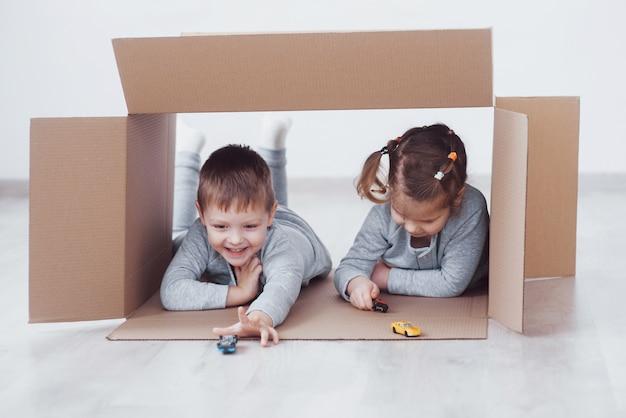 Brat i siostra dziecka bawiące się w kartonach w przedszkolu.