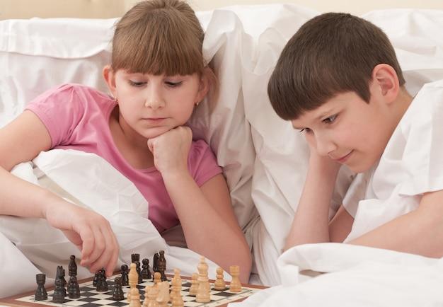 Brat i siostra grają w szachy w łóżku