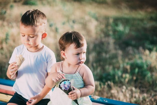 Brat i siostra jedzący lody na ławce na placu zabaw są bardzo urocze