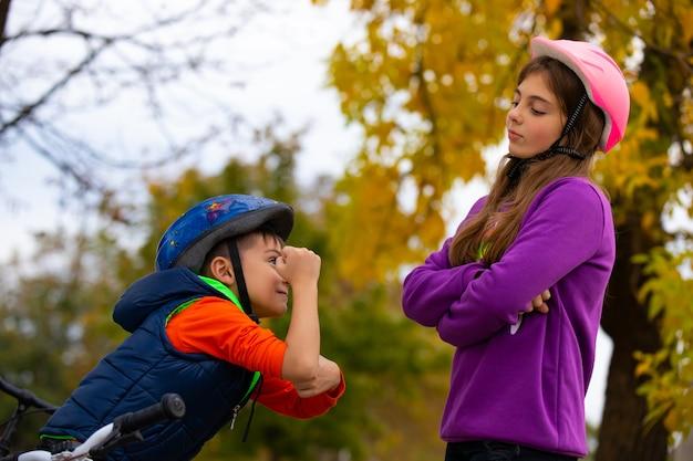 Brat i siostra kłócą się między jazdą na rowerach, kto jest silniejszy, chłopiec pokazuje swoją siłę. odpoczywają, uśmiechają się i patrzą na siebie. zdjęcie z jesiennego parku.
