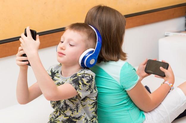 Brat i siostra korzystający z telefonów komórkowych, siedzący tyłem do siebie na kanapie w domu.