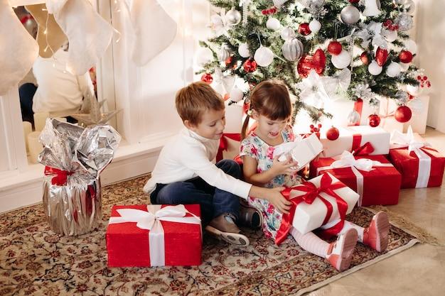 Brat i siostra otwierają prezenty świąteczne