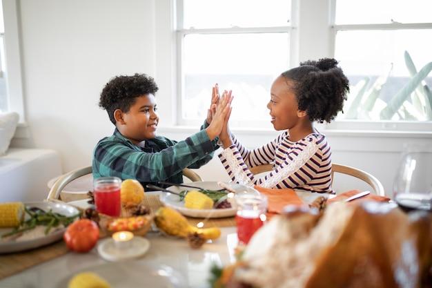 Brat i siostra przybijają piątkę po kolacji dziękczynnej