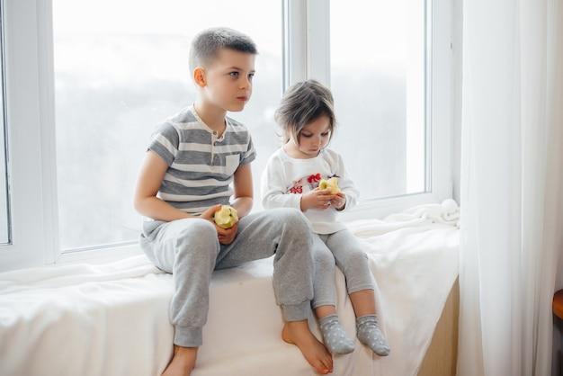Brat i siostra siedzą na parapecie, bawiąc się i jedząc jabłka. szczęście