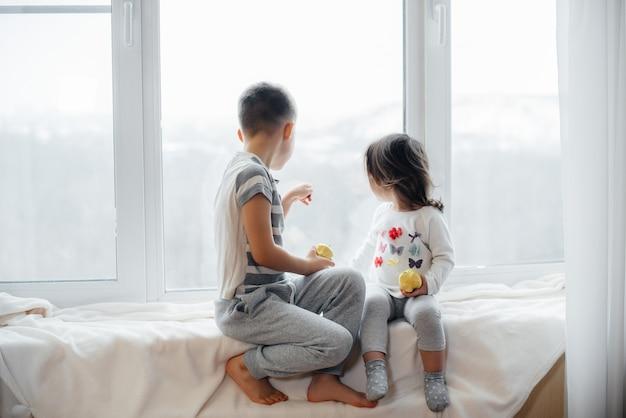 Brat i siostra siedzą na parapecie, bawiąc się i jedząc jabłka. szczęście.