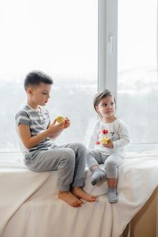 Brat i siostra siedzą na parapecie, bawiąc się i jedząc jabłka.