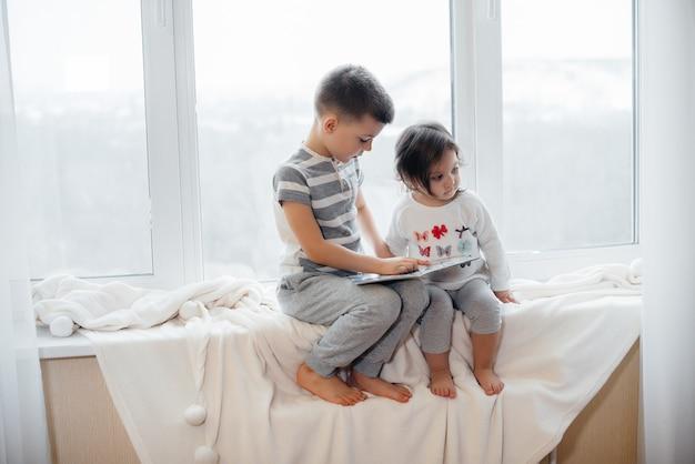 Brat i siostra siedzą na parapecie i czytają książkę. szczęście, rodzina