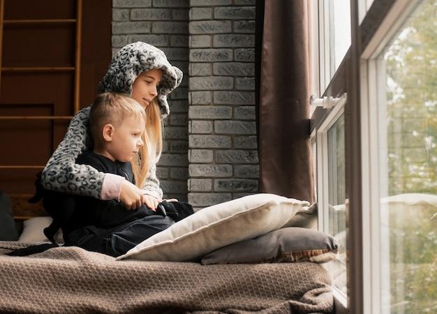 Brat i siostra siedzą przy oknie