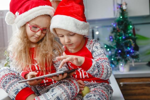 Brat i siostra siedzą w kuchni w czapkach mikołaja i patrzą na podkładkę. dzieci piszą list do świętego mikołaja
