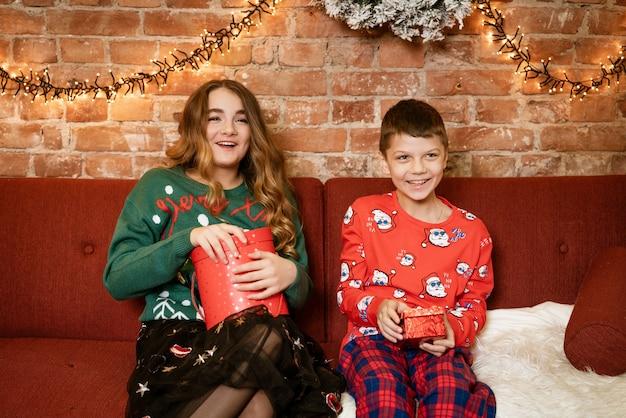Brat i siostra w domu na kanapie, otwierając prezenty świąteczne