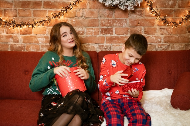 Brat i siostra w domu na kanapie szczęśliwego otwarcia noworocznych prezentów