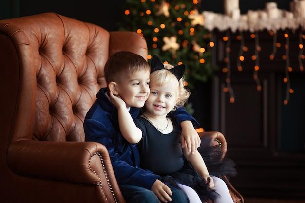 Brat i siostra w fotelu w noworocznym wnętrzu
