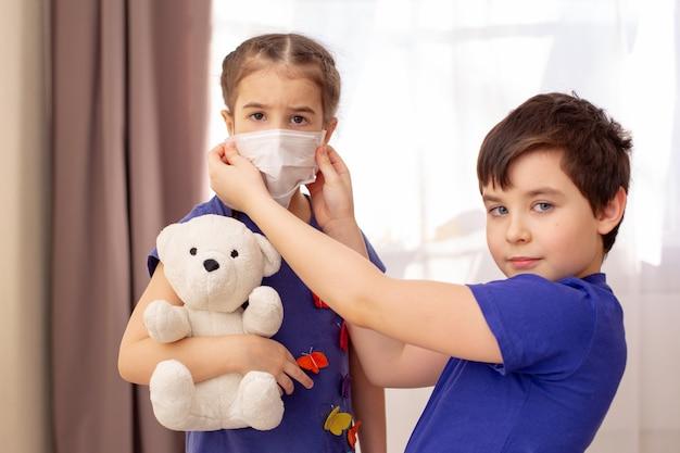 Brat nosi białą maskę medyczną dla swojej młodszej siostry