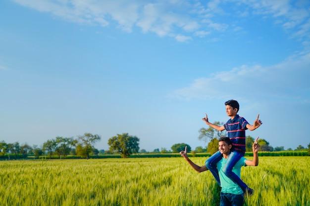 Brat piggyback jego młodszy brat w pszenicznym polu, wiejski ind