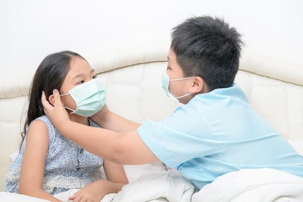 Brat pomaga swojej siostrze w chirurgicznej masce na łóżku,