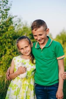 Brat przytula swoją siostrę. mali przyjaciele. zielona koszulka i zielona sukienka