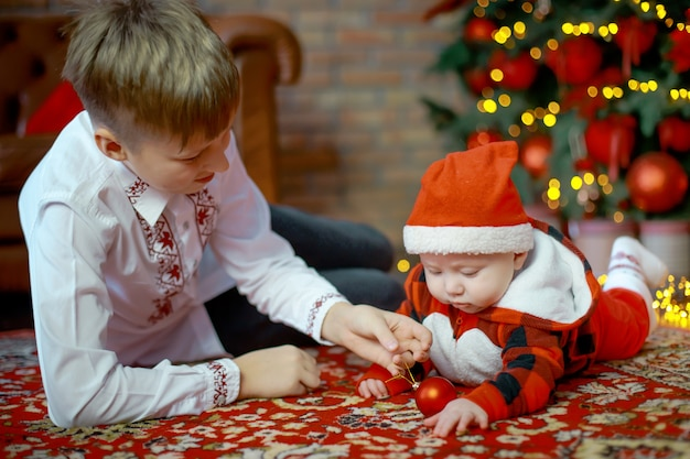 Brat z młodszą siostrą przy drzewie noworocznym. rodzina świętuje boże narodzenie. 6-miesięczny mały chłopiec uczy się czołgać