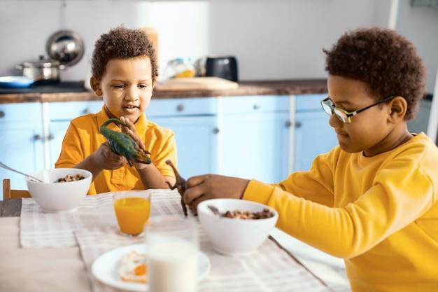 Braterska więź. mali chłopcy z kręconymi włosami jedzą śniadanie i bawią się swoimi zabawkowymi dinozaurami, rozmawiając ze sobą