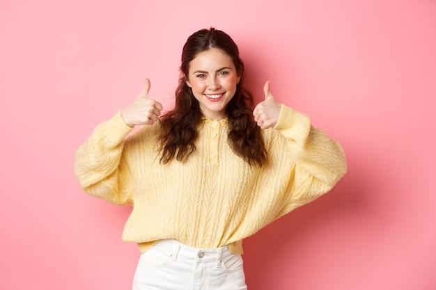 Brawo, bardzo dobrze. uśmiechnięta młoda kobieta pokazująca kciuki do góry z aprobatą, jak twój wybór, chwal dobrą rzecz, stojąc zadowolona przed różową ścianą