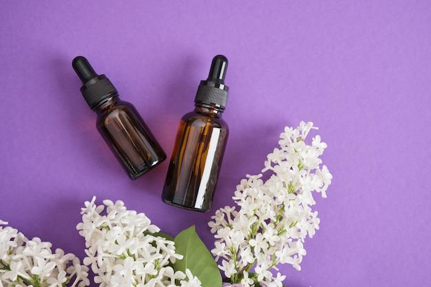 Brązowa butelka z zakraplaczem do olejków kosmetycznych lub serum i biały liliowy na jasnofioletowym tle, naturalne kosmetyki do pielęgnacji skóry twarzy i ciała. kopiuj przestrzeń widok z góry