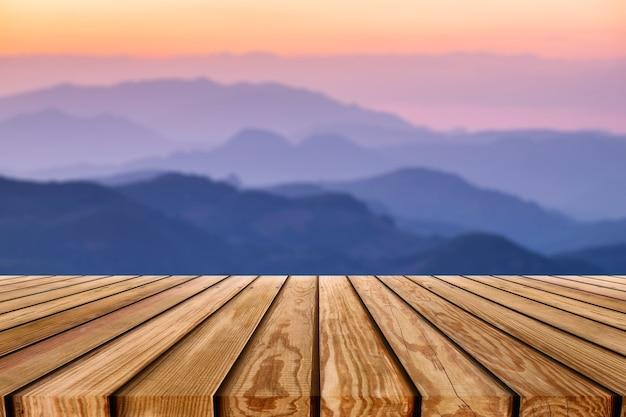 Brązowa drewniana deska w paski na warstwowym kolorowym górskim tle