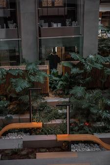 Brązowa drewniana ławka w pobliżu zielonych roślin