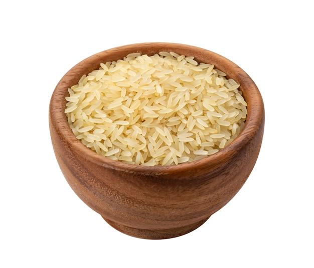 Brązowa drewniana miska z suchym niegotowanym ziarnem ryżu parzonego