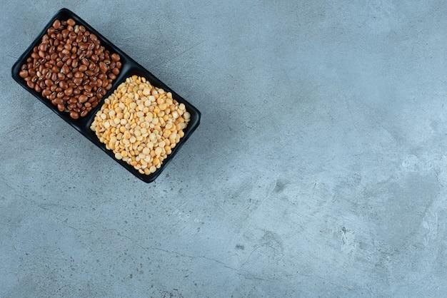 Brązowa fasola i groszek w czarnych ceramicznych spodkach. zdjęcie wysokiej jakości