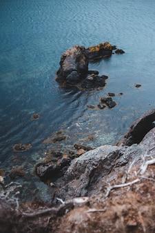 Brązowa formacja skalna na błękitnej wodzie morskiej w ciągu dnia