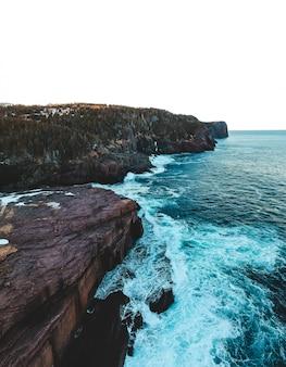 Brązowa formacja skalna obok błękitnego morza w ciągu dnia