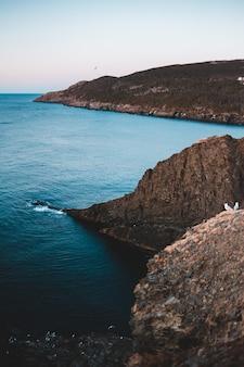 Brązowa formacja skalna w pobliżu błękitnego morza w ciągu dnia