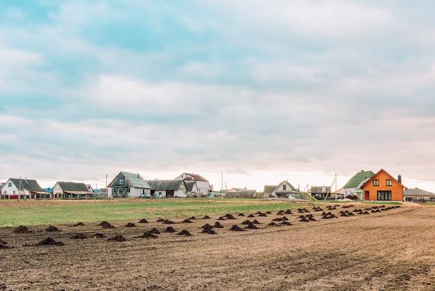 Brązowa gleba rolna pola. kupie świeży nawóz zwierzęcy przygotowany do sadzenia warzyw polowych.