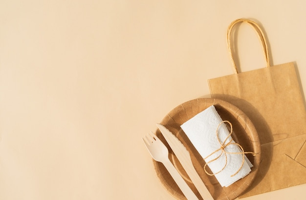 Brązowa jednorazowa torba i zastawa stołowa, talerz i drewniany widelec, nóż na brązowej powierzchni płasko leżał widok z góry